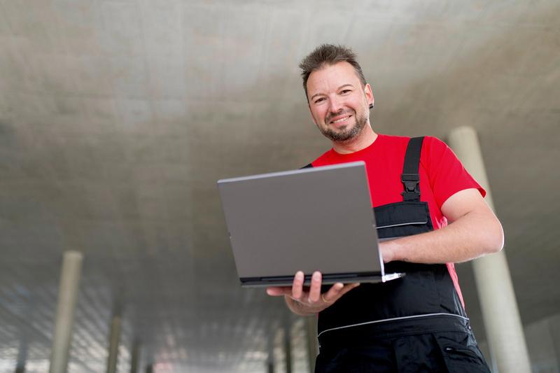 Schreiner arbeitet am Laptop
