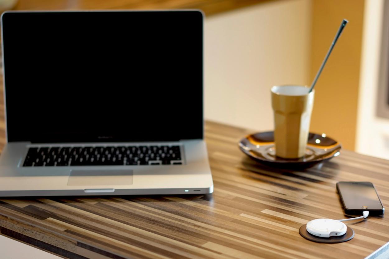 Laptop mit Kaffee und Mobiltelefon auf Tisch