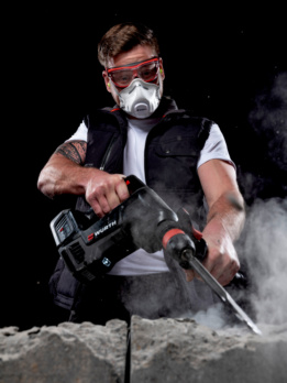Mann mit Bohrhammer, der Atemschutzmaske trägt