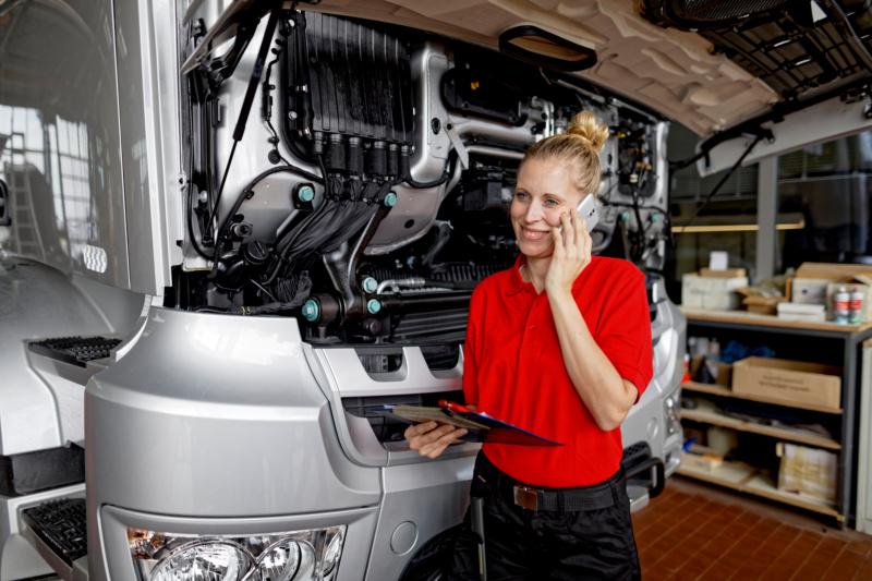 Mechanikerin telefoniert mit Kundenservice