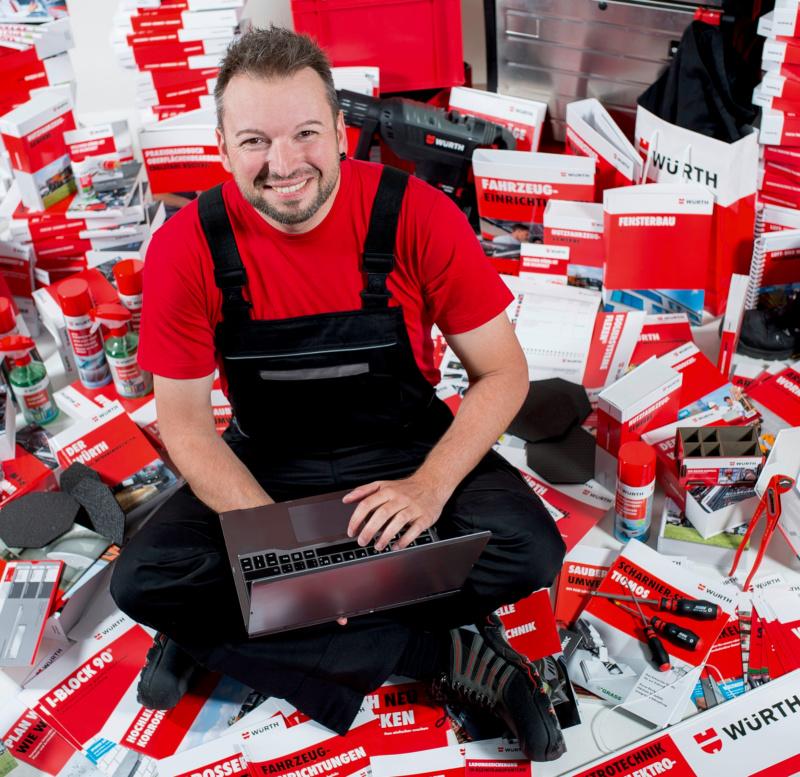Mann mit Laptop sitzt auf Katalogen