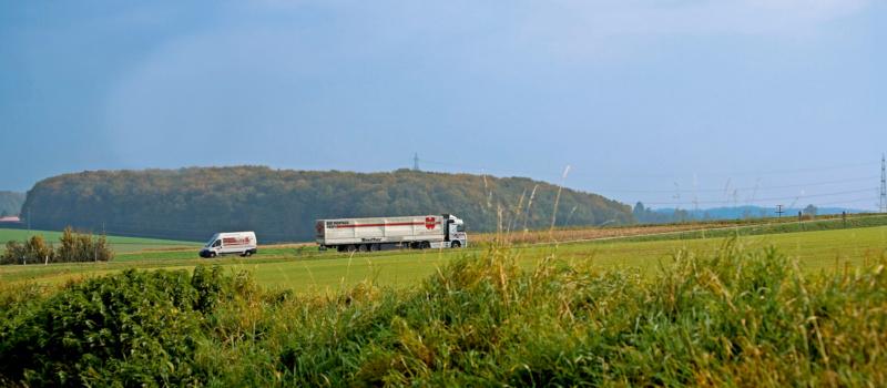 LKW und Kleintransporter auf Landstraße zwischen Feldern