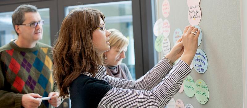Frau befestigt Metaplankarten an Board